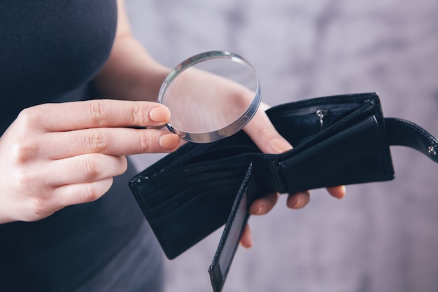 Girl holding a magnifying glass and wallet