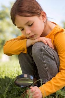 Девушка держит увеличительное стекло среднего выстрела