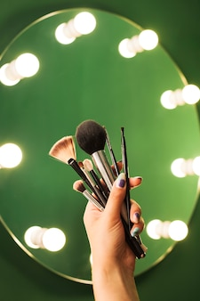 Girl holding make up brushes in front of a mirror