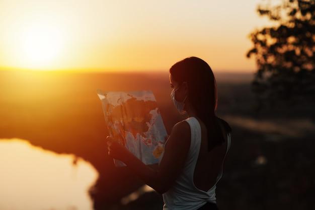 Девушка держит карту мира, она в маске на поверхности заката. туристическая девушка изучает маршрут.