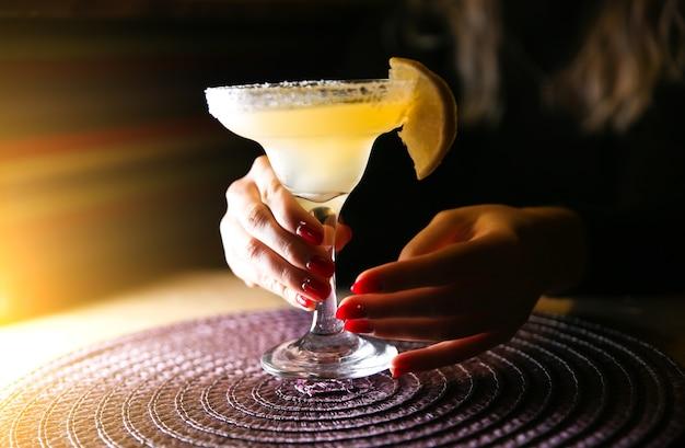 レストランのテーブルでマルガリータカクテルを保持している女の子。アルコール飲料。美しい手。