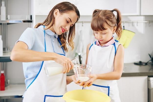 母親が新鮮な冷たいミルクを注いでいるときに計量瓶を持っている女の子