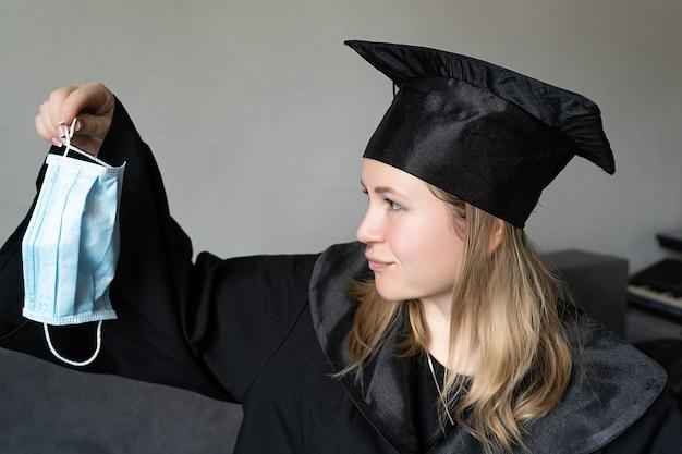 회색 배경에 졸업 모자와 의료 마스크를 들고 소녀