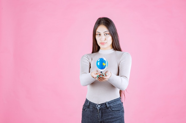 Girl holding a mini globe and smiling