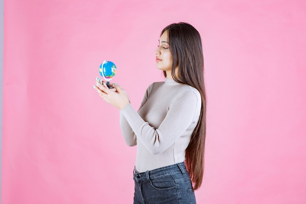 Girl holding a mini globe and studying it attentively