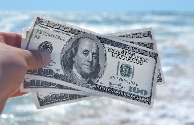 Девушка держит банкноту в 300 долларов на фоне морского океана