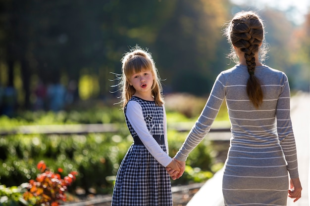 暖かい日を屋外で振り返って母の手を握って女の子。