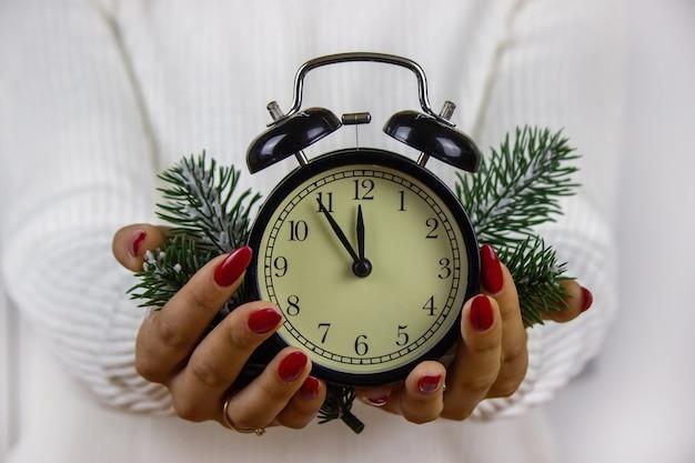 새해 장난감, 선물, 시계를 손에 들고 있는 소녀. 크리스마스 개념입니다. 선택적 초점
