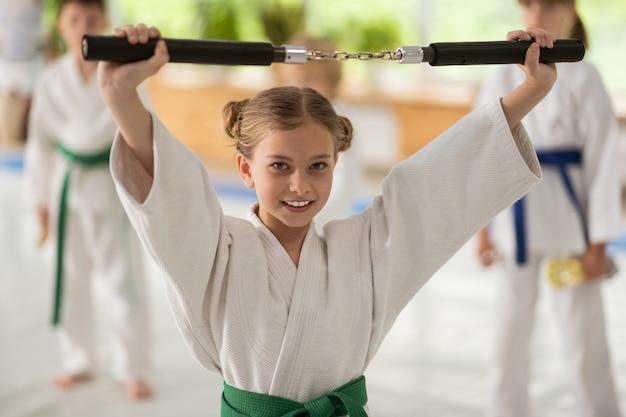 Девушка держит нунчаки во время занятий боевыми искусствами