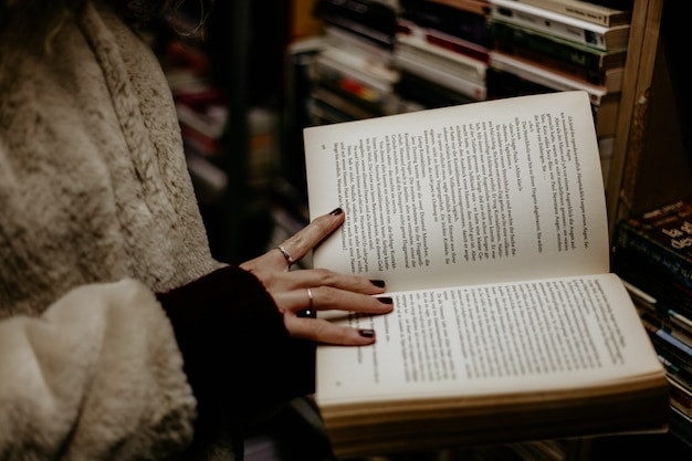 Girl holding an open book in her hands in the book shop.