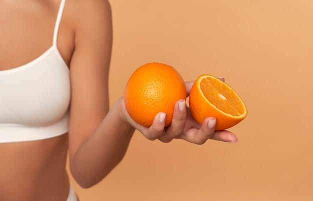 베이지 색에 고립 된 흰색 속옷에 오렌지 반쪽을 들고 소녀