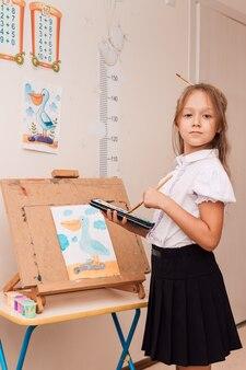 Девушка держит в руках краски и кисть
