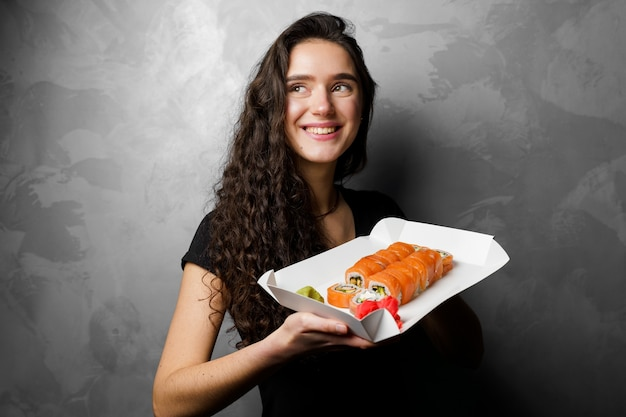 필라델피아를 들고 있는 소녀는 회색 배경에 종이 상자에 롤백합니다. 스시, 음식 배달.