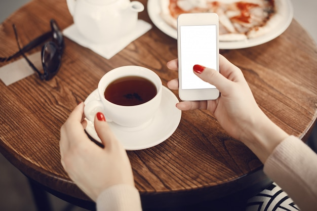 Girl holding phone with empty screen at cafe