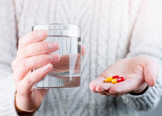 그녀의 손에 알 약과 물 한 잔을 들고 소녀