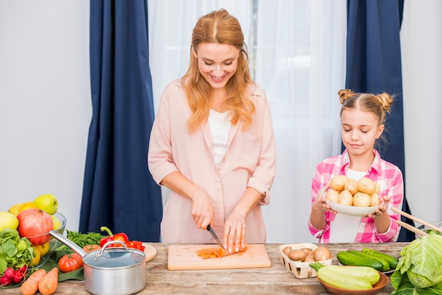 Girl holding potatoes plate standing near the smiling young woman cutting the carrot with knife on table