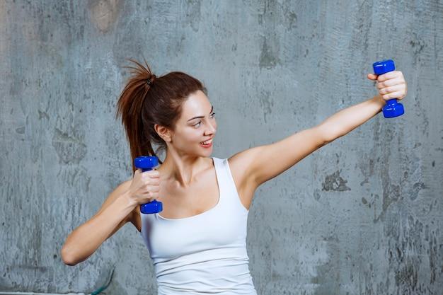 軽いキログラムの紫色のダンベルを持って、両腕を動かしている女の子。