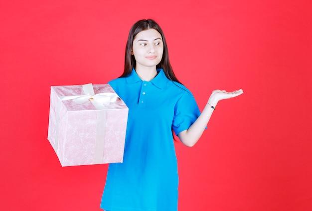 Ragazza con in mano una scatola regalo viola avvolta con un nastro bianco e che invita qualcuno a presentare il regalo