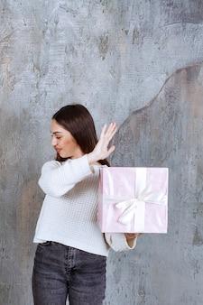 Ragazza in possesso di una confezione regalo viola avvolta con un nastro bianco e fermando qualcosa.