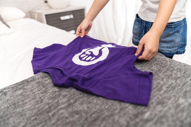 Girl holding a purple t-shirt with the symbol of the international feminist working women's day on her bed in her room