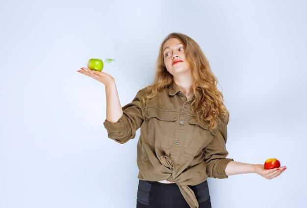赤と緑のリンゴを両手に持っている女の子。