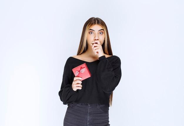 Ragazza con una confezione regalo rossa e sembra terrorizzata. foto di alta qualità
