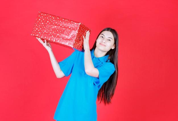 Ragazza con una scatola regalo rossa con puntini bianchi sulla spalla