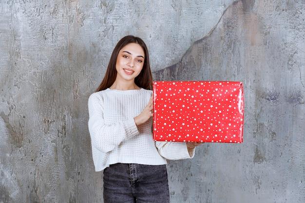 Ragazza con una confezione regalo rossa con puntini bianchi sopra
