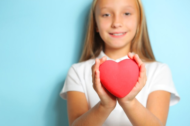 Girl holding a red heart in her hands on a blue background