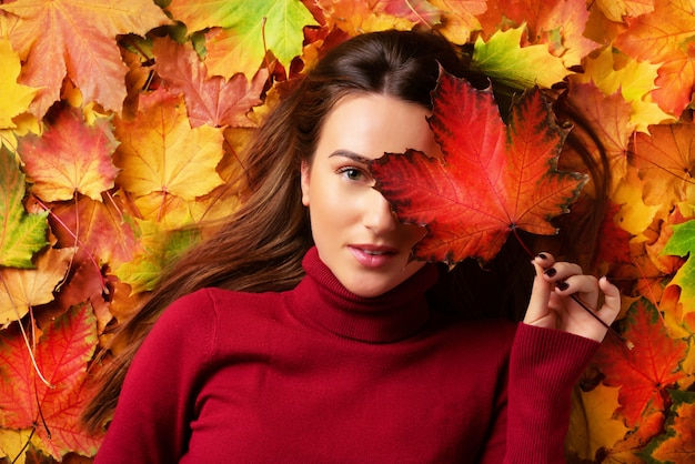 Girl holding red maple leaf in hand over colorful fallen leaves background. gold cozy autumn concept.