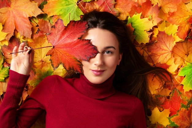 Girl holding red maple leaf in hand over colorful fallen leaves background.