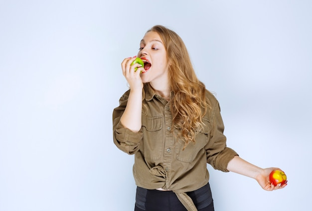 Girl holding a red peach and biting a green apple.