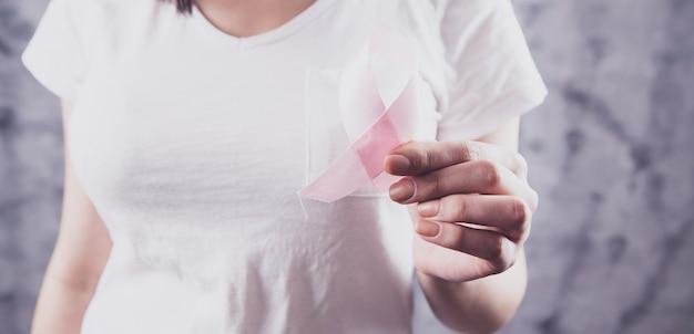 Девушка держит красную ленту знак рака