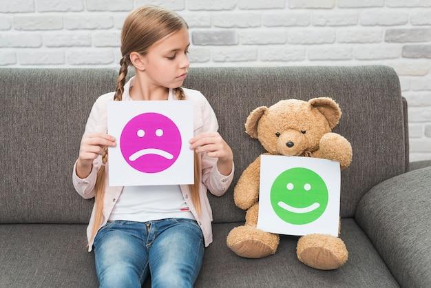 Девушка держит грустные смайлики бумаги, глядя на плюшевого мишку со счастливыми смайликами