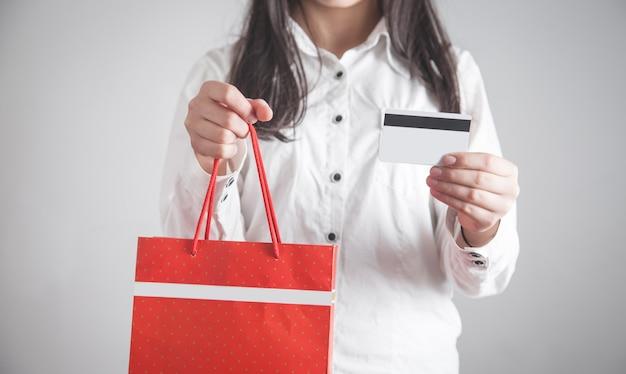 Девушка держит хозяйственную сумку с кредитной картой. покупка товаров