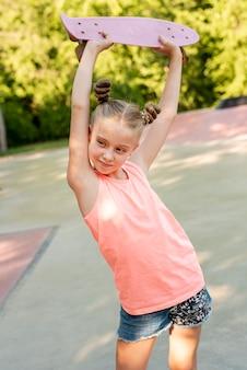 Girl holding skateboard over head