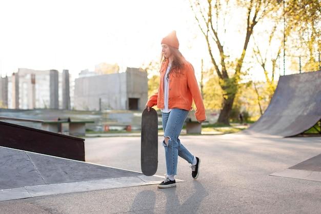 Girl holding skateboard outdoors full shot