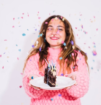 Girl holding slice of chocolate cake surrounded by confetti