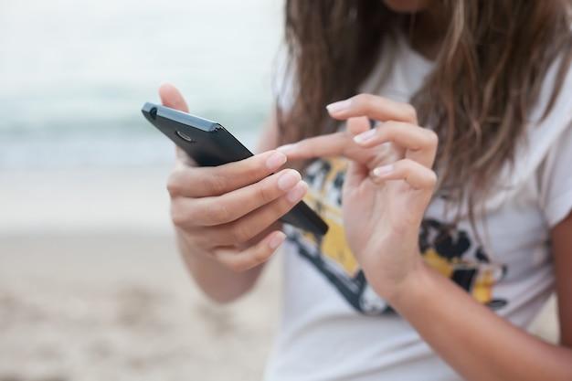 Девушка держит смартфон на берегу