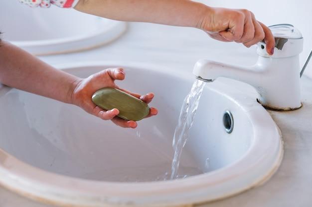 세면 대에서 손을 씻는 동안 비누를 들고 소녀