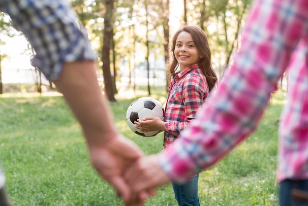 Girl holding soccer ball looking at her parent holding hand in park