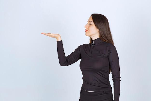 그녀의 손에 뭔가 들고 그것을 제시하는 소녀.