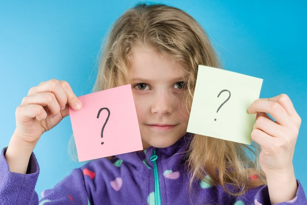 Girl holding stickers with question marks