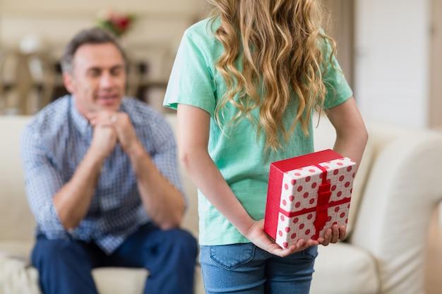 リビングルームで彼女の父の驚いた贈り物を持って女の子