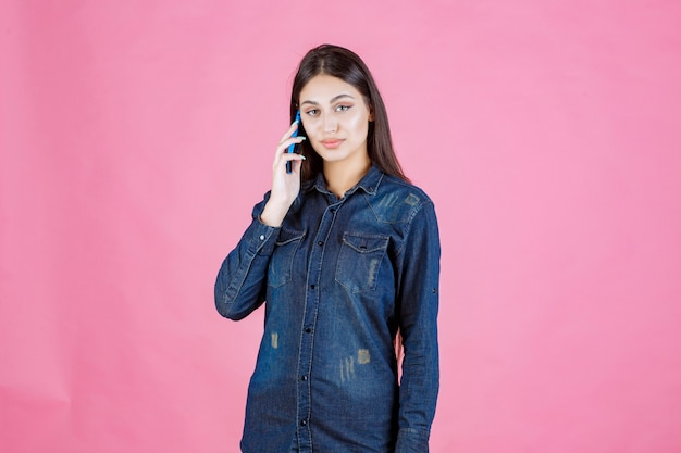 Ragazza che tiene parlando al suo smartphone blu
