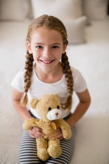 Girl holding a teddy bear on bed in bedroom