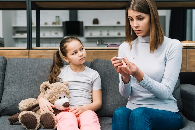 Girl holding teddy bear sitting near the young woman looking at temperature