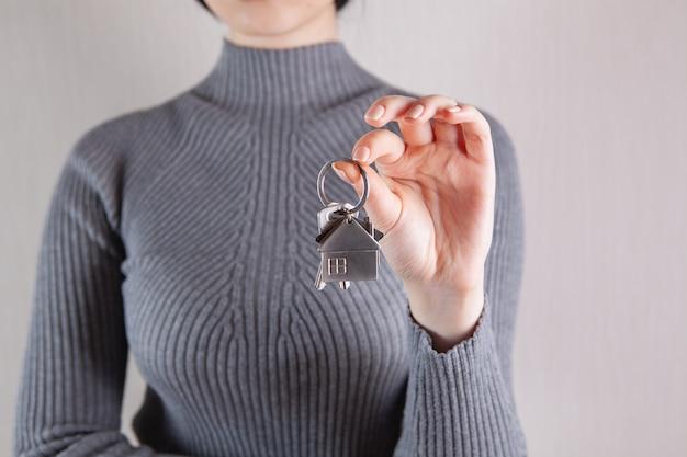 그녀의 손에 새 집의 열쇠를 들고 소녀