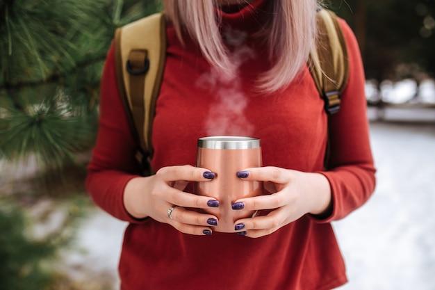 Девушка держит термокружку с горячим дымящимся чаем в зимнем лесу