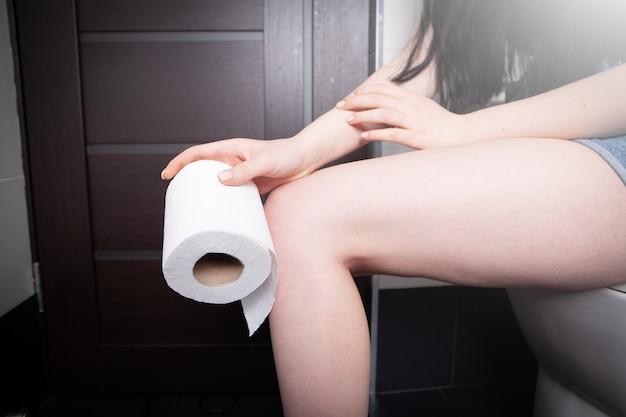 Девушка держит в руках туалетную бумагу.